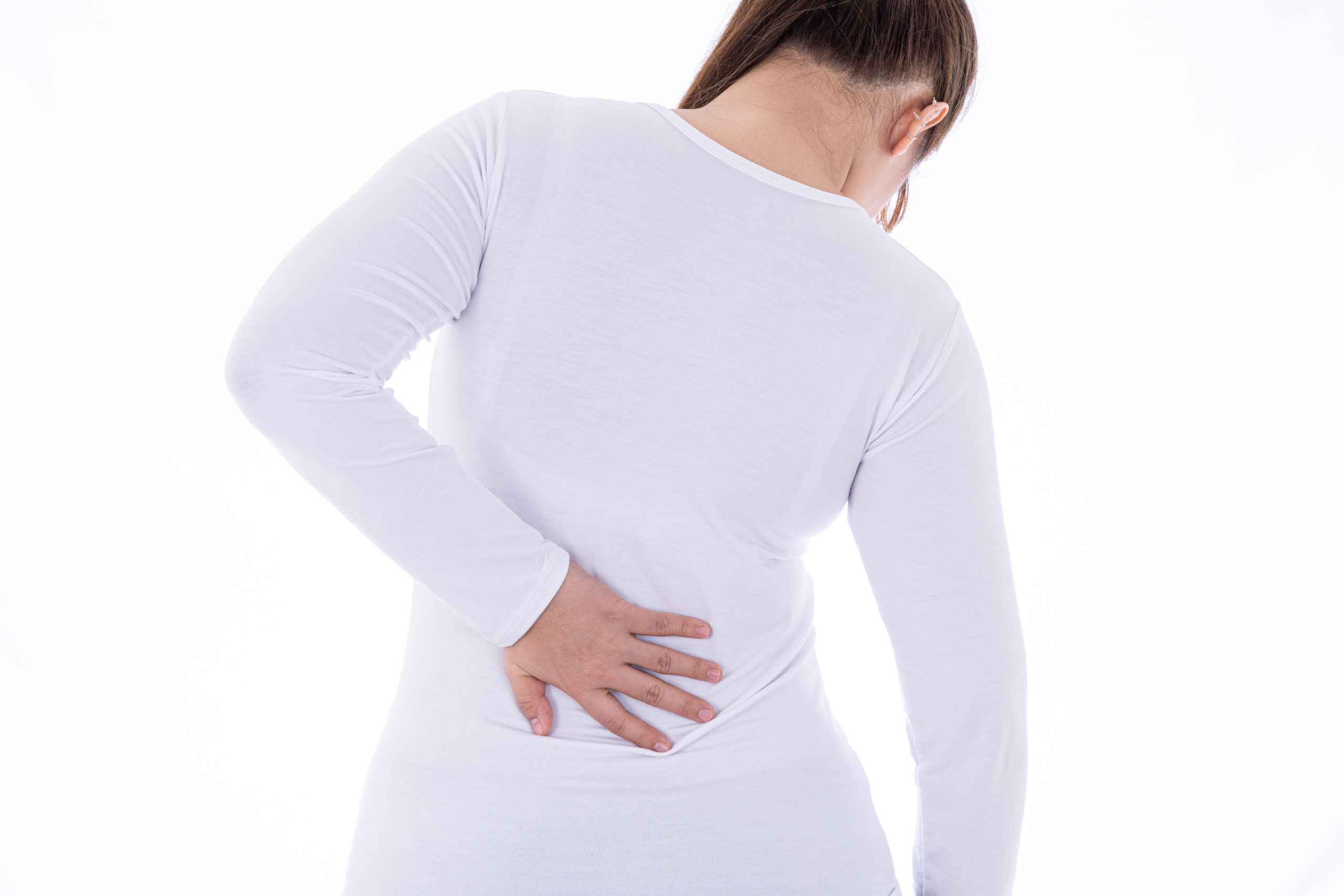A woman feeling exhausted and suffering from waist and back pain and injury on isolated white background. Health care and medical concept.